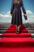 stock photo of stairway  - Elegant woman in black coat climbing a red carpet stairway - JPG