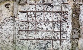 stock photo of mortar-joint  - Grey concrete surface with visible blocks joints and reinforcement bars - JPG
