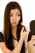 picture of blush  - Cute Asian American teen applying blush mirror - JPG