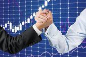stock photo of wrestling  - Businessmen hands engaged in arm wrestling on stock chart background - JPG