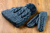 foto of knitted cap  - gray knitting cap and mittens on wooden background - JPG
