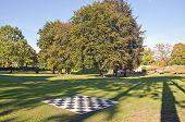 stock photo of manor  - big outdoor empty chess board in autumn manor park - JPG