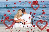 pic of couple sitting beach  - Affectionate couple sitting on the sand at the beach against love heart pattern - JPG