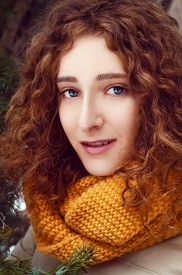 image of auburn  - Attractive young woman with curly auburn hair near pine tree with yellow snood and mittens - JPG