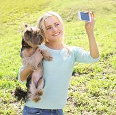 picture of yorkshire terrier  - Happy woman and yorkshire terrier dog having fun takes selfie portrait on the smartphone - JPG