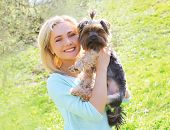 picture of yorkshire terrier  - Sunny portrait of happy young woman owner with yorkshire terrier dog in the park - JPG