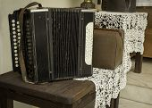 stock photo of accordion  - vintage accordion standing on the wooden table - JPG