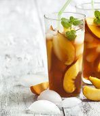 picture of iced-tea  - Peach Ice Tea in glass cup on wooden table - JPG