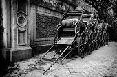 pic of rickshaw  - Black and white image of traditional hand pulled Indian rickshaws parked together in front of a old building in Kolkata - JPG