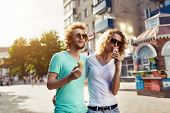 image of licking  - Handsome young couple walking together and licking ice cream - JPG
