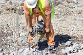 image of reinforcing  - Construction worker holding jackhammer and breaking reinforced piles in the ground - JPG