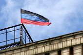 pic of rebel flag  - Donetsk Republic flag located on one of the buildings of Donetsk on background the sky - JPG