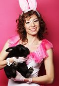 picture of horny  - Young happy woman with black rabbit over pink background - JPG