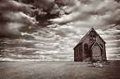 Abandoned church in the desert, with stormy skies.  Monotone image, with added grain.