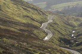 stock photo of long winding road  - Long shot of road snaking along hillside - JPG
