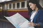 Asian Traveler Woman Looking Map At Train Station Find Destination. Happy Backpacker Girl Lost In Th poster