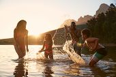 Family Enjoying Evening Swim In Countryside Lake poster