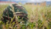Military camouflage helmet putted down on the ground. Anti-war symbol. Soldier got tired of war. Clo poster