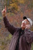 picture of older men  - handsome man in wilderness on cell phone 242 pointing - JPG