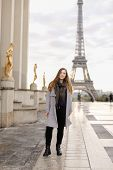 Young Caucasian Woman In Grey Coat Standing On Trocadero Square Near Gilded Statues And Eiffel Tower poster