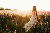 Young Woman Walking On Flower Field At Sunset On Background. Horizontal View With Copy Space. poster