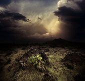 stock photo of rare flowers  - Storm dark clouds over volcanic valley with grass and rocks - JPG