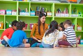 Asian Female Teacher Teaching Mixed Race Diversity Group Of Kids Reading Book Sitting On Library Flo poster