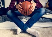 Teenage boy in a bedroom holding a basketball hobby aspiration and loneliness concept poster