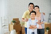 Group Portrait Of Happy Asian Family Of Three Looking At Camera With Wide Smiles While Distracted Fr poster