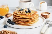 Pancakes With Nuts, Honey And Fruits For Breakfast. Stack Of American Pancakes. Tasty Pancakes On Wh poster