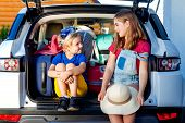 Little Sister And Brother Are Sitting In The Trunk Of A Car With Suitcases. Travel By Car Family Tri poster