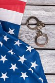 American Flag And Handcuffs, Top View. Usa Flag And Old Metal Handcuffs On Vintage Wooden Background poster