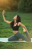 Woman Practicing Yoga Performing Yoga-asanas. Young Attractive Slim Girl In Bodysuit Relaxing And Do poster