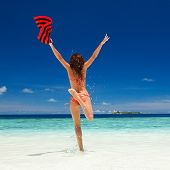 Happy young woman jumping on the beach. Happy lifestyle. White sand, blue sky and crystal sea of tro poster