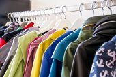 Colorful softshell coats on rack with hangers. Fashion conception.  poster