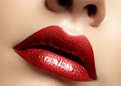 Close-up Macro Shot Of Female Mouth. Glamour Red Lips Makeup With Sensuality Gesture. Metalic Gloss  poster