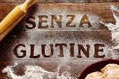 high angle view of a wooden table sprinkled with a gluten free flour where you can read the text sen poster