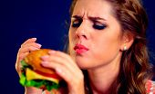 Woman eating fast food. Girl enjoying delicious hamburger, eyes closed. Pretty female student with s poster