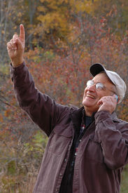 pic of older men  - handsome man in wilderness on cell phone 242 pointing - JPG