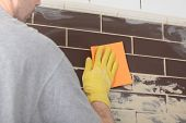 stock photo of grout  - Contractor grouting ceramic tiles on a wall - JPG