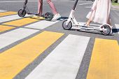 Woman Legs And Man Legs Walking With Scooters On Cross Road poster