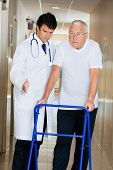 picture of zimmer frame  - Doctor helping senior patient walk down hallway using Zimmer frame - JPG
