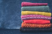 Pile Of Knitted Woolen Sweaters Autumn Colors. Clothes With Different Knitting Patterns Folded In St poster