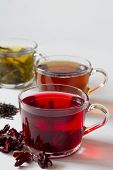 Red Hot Hibiscus Tea With Dry Flowers. Healthy Lifestyle.three Glass Cups With Black, Red And Green  poster