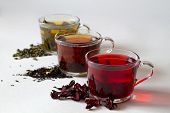 Three Glass Cups With Black, Red And Green Tea With Dry Leaves On A White Background. Red Hot Hibisc poster