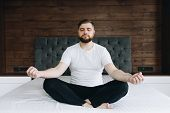 Handsome Caucasian Man Meditating Calmly And Being Mindful On His Bed In Bedroom poster