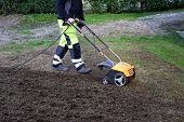 A Man Cuts Moss In The Garden With An Aerator. Concept: Lawn Aeration Before Planting Lawn Grass. Ga poster