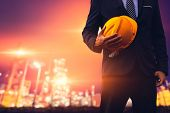 Construction Engineer In Business Suit  Holding Yellow Safety Hard Hat Security Equipment On Constru poster