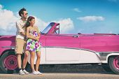 Couple driving pink vintage car on summer road trip travel fun.. Happy smiling young couple during s poster