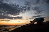 Yoga woman doing exercise on the ocean coast at dusk. poster